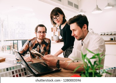 Group of beautiful designers in casual clothes is looking at color swatches. Creative team of graphic designers working on new project using color swatches and sketches.