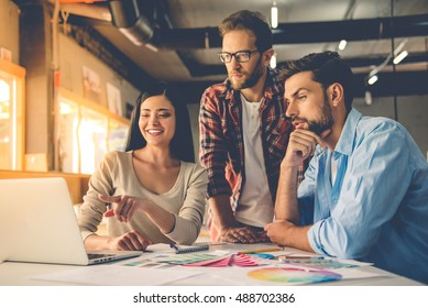 Group of beautiful designers in casual clothes is using a laptop, discussing affairs and smiling while working in studio