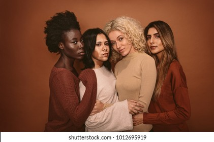 Group of beautiful female friends standing together on brown background. Multi ethnic women in studio looking at camera.