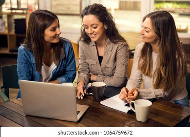 Group of beautiful female friends studying together