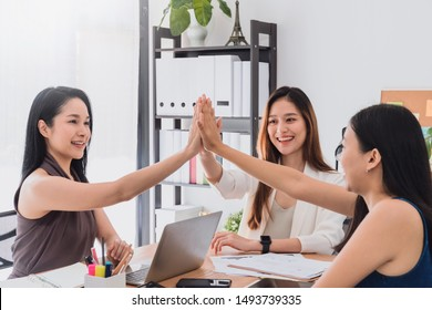 Group of beautiful  happy Asian women meeting and giving high five hand touch together in office space to discussion or brainstorm business startup project.Concept of teamwork of empower woman.
