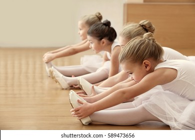 Group of beautiful little ballerinas doing exercises on the floor