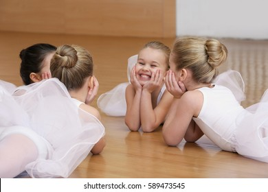 Group of beautiful little ballerinas resting on the floor