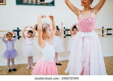 Group of beautiful little girls practicing ballet at dancing class.