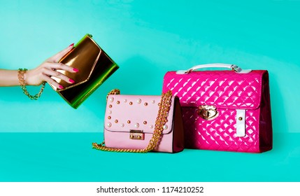 Group of beautiful purses bags and woman hand holding one handbag.  Shopping image.