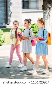 group of beautiful schoolgirls with notebooks walking together after school