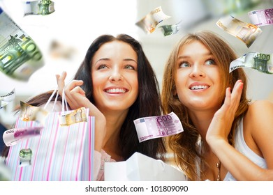 Group of beautiful shopping women with bags and smiling. Money flying around them. Spending money non stop concept