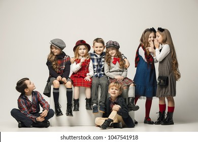 The group of beautiful teen girls and boys on a pastel studio background. Stylish young teen girls posing at studio. Classic autumn style. Teen and kids fashion concept. children's fasion concept