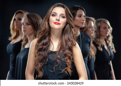 Group of beautiful women. Attractive young woman in black dress with long hair looking at camera and her friends standing in front her back against black background.