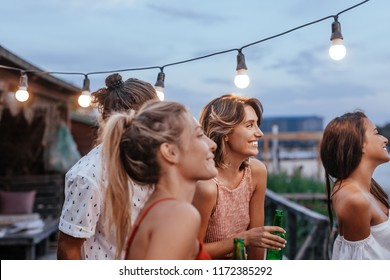 Group of beautiful women and man standing on terrace and enjoying summer vacation.