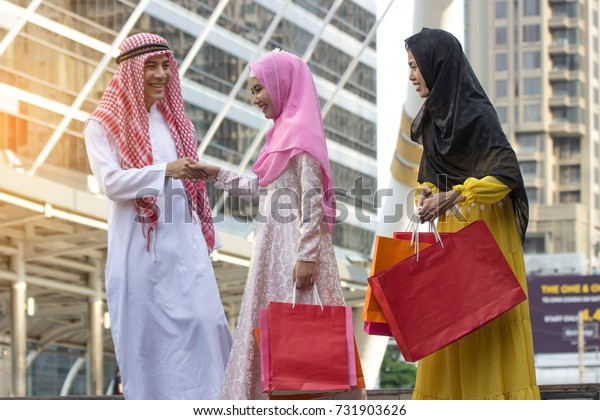 A group of beautiful women and young men who worship Islam are shopping in the mall. And hold the bag in her hand.