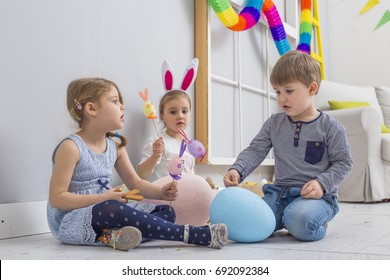 Group of beautiful young kid's  playing with Easter eggs and a bunny doll on a laminated floor