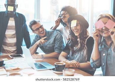 Grupo de jovens bonitos na mesa do café com laptop se divertindo juntos jogando jogo de nome com notas pegajosas na testa, rindo