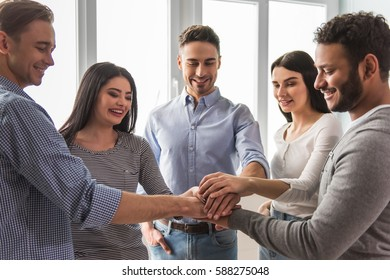 Group of beautiful young people in casual clothes are putting hands together and smiling