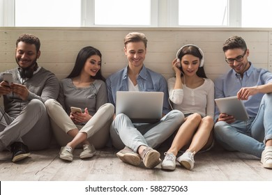 Group of beautiful young people in casual clothes using gadgets and smiling while sitting together on the floor