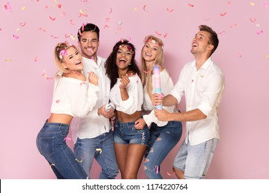 Group of beautiful young people partying together, posing on pink studio background.