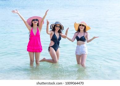 Group of beautiful young single women having fun on beach. Doing selfie together, wearing bikini, beach hat.