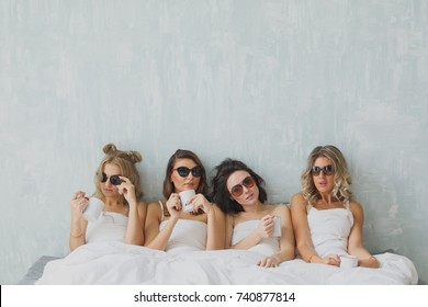 group of beautiful young woman napping in her bed after party in sunglasses. Sexy stylish young woman model lying in bed.