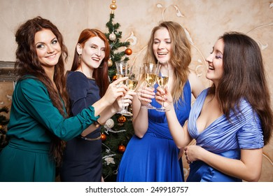 Group of beautiful young women with glasses of champagne celebrating New Year