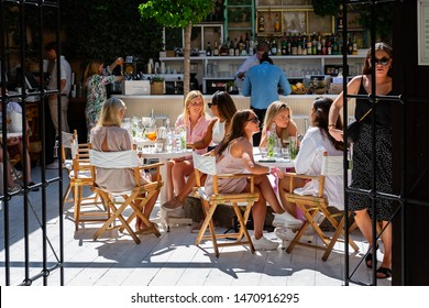 Group of beautiful young women sat at tables chatting and drinking cocktails in Visby, Gotland, Sweden on 20 July 2019