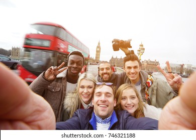 A group of best friends have a lot of fun at the trip in London making a selfie for remember the funny time in England. Multiracial young hipster people make sightseeing and visit Big Ben tower.