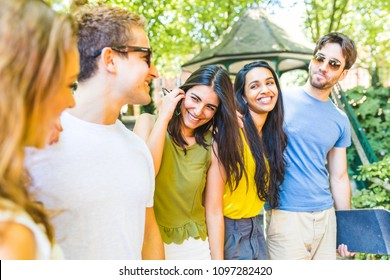 Group of best friends at park talking and having fun. Multi ethnic people enjoying time together and laughing in London. Carefree and lifestyle concepts with real people