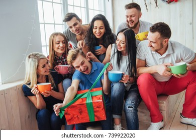 Group of best friends at party. smiling and cheerful people sitting on the stairs and a cup of coffee and greet the birthday, a great gift.