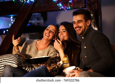 Group best friends sitting at home on pleasant  evening and watching a comedy movie .Watching late night show.
