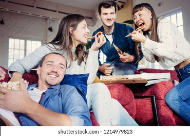 Group of best friends spending time at home party. Eating pop corn and pizza together. Multi ethnic people