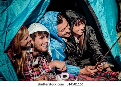 Group of best friends taking a selfie in camping while it is raining - Concept of carefree youth and freedom outdoors in the nature - Young people during vacations