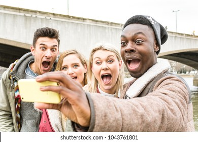 Group of Best Student Friends Taking a Selfie Outdoor at City Tour. Two Couples Having Fun Together, Making Photo for Memory with Funny Pose, Grimace and Looking at  Phone. Happy Friendship Concept.