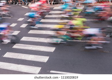 Group of bicyclers slashing the frame on the asphalt, blurred by their swift motion