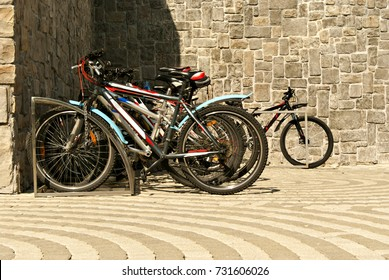 a group of bicycles in the parking lot for bicycles on the background of a stone wall and a sidewalk