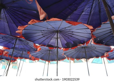 Group of big red and blue beach umbrella.