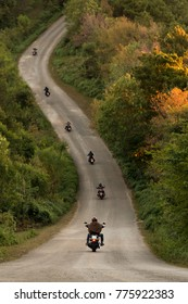 Group of a bikers on the highway between beautiful green tree forest, motorcyclists traveling along mountains road, freedom and active lifestyle concept. - Depth of field.