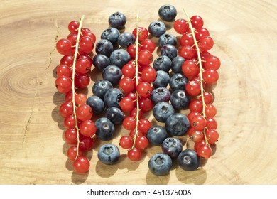 Group of bilberries and red currant placed on a golden dish with white isolated background.