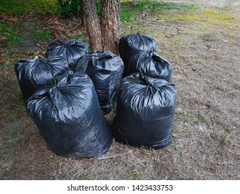 Group of Black Plastic Bags Filled with Trash on Grass Field