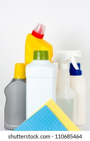 Group of blank plastic bottles used for cleaning supplies and two colourful washing cloths on white