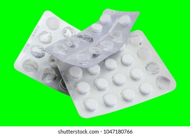 Group blister pack used medicine tablets and drugs isolated on green. Photo.