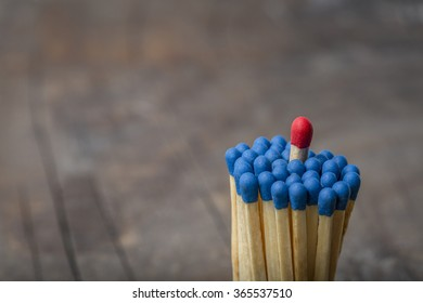 Group of blue matches with one red match sticking out on rustic wooden background