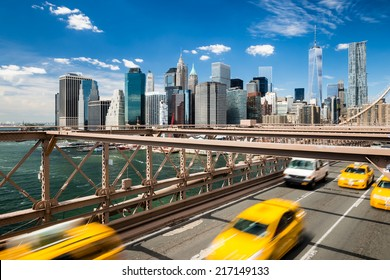 Group of blurred typical yellow New York cabs crossing the Brooklyn Bridge with the Manhattan skyline with blue sky with few clouds  in the background