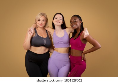 Group Of Body Positive Females With Different Figure Types Posing In Sportswear Over Brown Background In Studio, Three Happy Multi-Ethnic Women Embracing And Enjoying Their Beauty, Copy Space