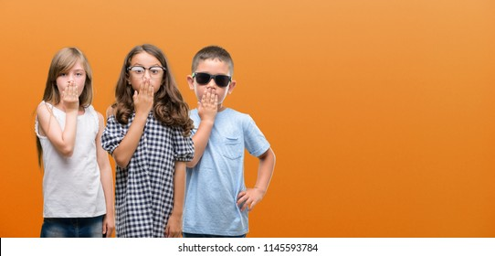Group of boy and girls kids over orange background cover mouth with hand shocked with shame for mistake, expression of fear, scared in silence, secret concept