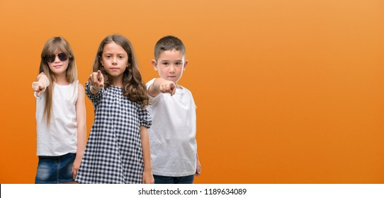Group of boy and girls kids over orange background pointing with finger to the camera and to you, hand sign, positive and confident gesture from the front