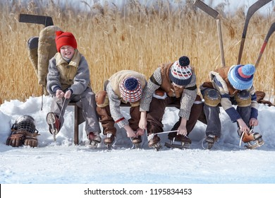 Group of boys are changed for hockey on a bench at a local lake