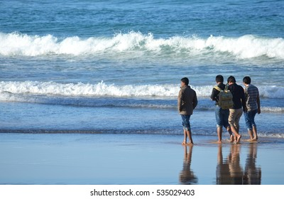 Group of boys, four guys walking on the beach.