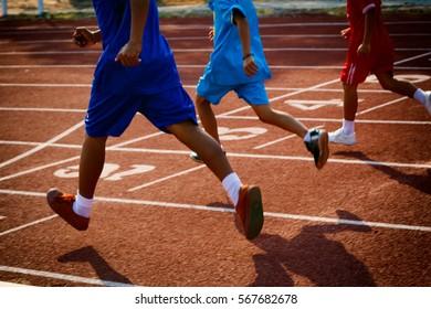 Group of boys running on running track in the stadium