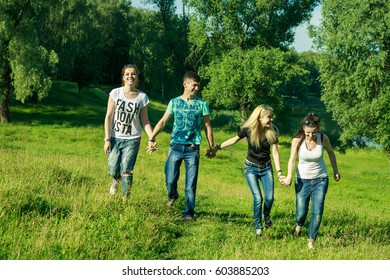 a group of boys and three girls. people, freedom, happiness, and teenage concept - group of happy friends wearing sunglasses go out and have fun on a background of green meadows and trees