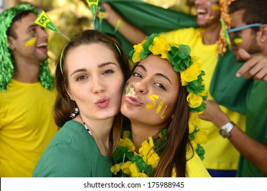 Group of Brazilian girls soccer fans commemorating victory posing kissing.