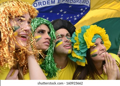 Group of Brazilian soccer fans concerned with the national team performance with the flag of Brazil swinging in the air.